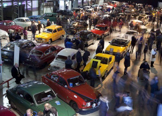 """Visitors look at various Saab car models on display in a hangar at the former Valkenburg Airbase, near the Hague January 15, 2012. Members of a Saab fan club from 42 countries organized a """"Saab Day"""", where all the models produced by the 64-year-old carmaker were displayed, to pay tribute to the Saab brand name and the employees who lost their jobs after the car company went bankrupt, according to organisers. Saab was declared bankrupt by a court last month, ending a nine-month battle by its Dutch owner Swedish Automobile NV to stay afloat. It has not made any vehicles since April and several rescues have failed. REUTERS/Michael Kooren (NETHERLANDS - Tags: TRANSPORT BUSINESS SOCIETY)"""