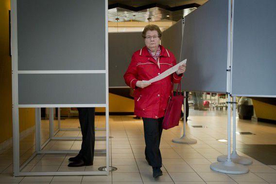 Een kiezer loopt het stemhokje uit bij lokale verkiezingen in Alphen aan de Rijn.