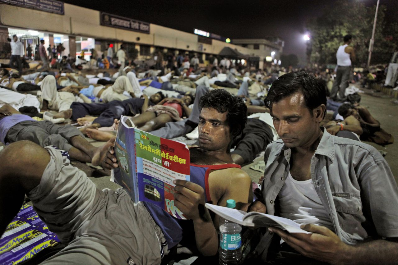 Two of candidates who have arrived to take an Indian railway recruitment examination, study as others sleep at night at the railway station in Allahabad, India, Sunday, June 3, 2012. About 130,000 candidates are appearing for the exam at numerous centers spread across the city. India's mammoth rail network is truly a mass transportation system, with its 40,000 miles (64,000 kilometers) of railway track cut through some of the most densely populated cities, flanked by shanty towns, in the nation of 1.2 billion people.(AP Photo/Rajesh Kumar Singh)