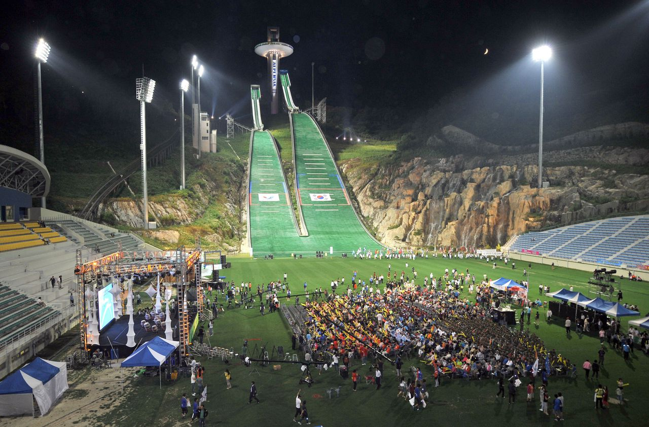 South Koreans gather at the ski jump stadium for night rally to support Pyeongchang's bid for the 2018 Winter Olympics in South Korea's mountain resort of Pyeongchang, 180 kms east of Seoul, on July 6, 2011 as they wait for a vote by the International Olympic Committee in the South African city of Durban to pick the venue. AFP PHOTO/JUNG YEON-JE