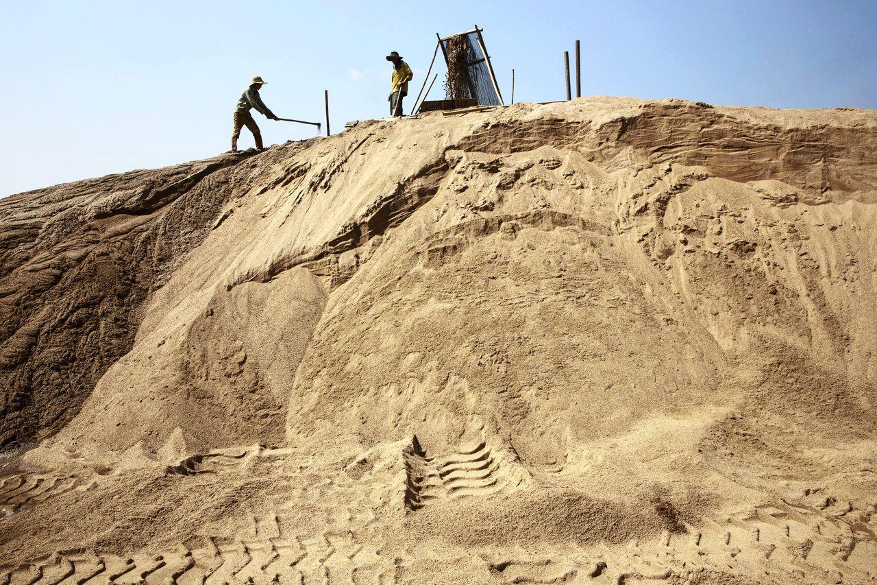 Arbeiders aan het werk op een plek waar zand wordt gewonnen, in Myanmar.