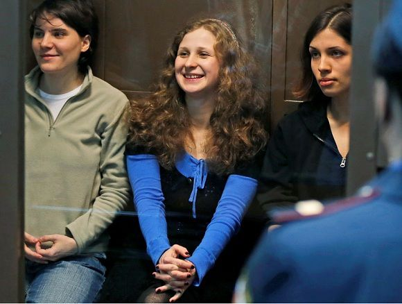 Caption: RETRANSMISSION FOR ALTERNATIVE CROP - Feminist punk group Pussy Riot members, from left, Maria Alekhina, Yekaterina Samutsevich, center, and Nadezhda Tolokonnikova sit in a glass cage at a court room in Moscow, Wednesday. Oct. 10, 2012. Moscow appeals court freed Yekaterina Samutsevich of jailed band Pussy Riot but upheld a prison sentence for Nadezhda Tolokonnikova and Maria Alekhina. The judge ruled that Yekaterina Samutsevich's sentence should be suspended because she was thrown out of the cathedral by guards before she could take part in the performance.(AP Photo/Sergey Ponomarev)