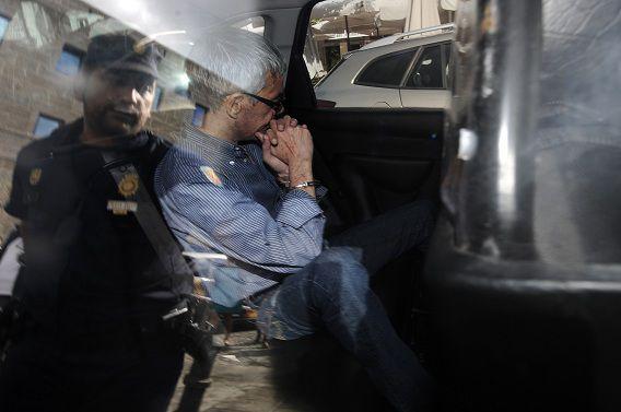 Machinist Francisco Garzon verlaat het politiebureau om naar de rechtszaal van Santiago de Compostela te worden gereden.