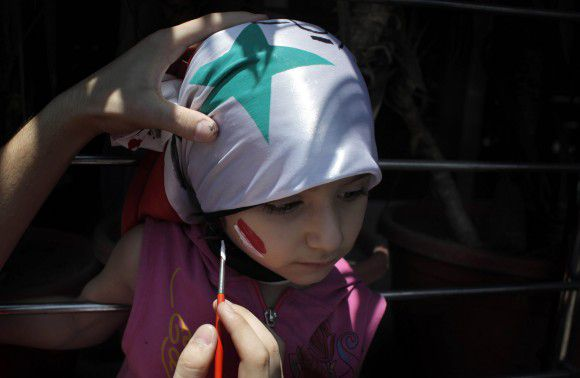 A Protester paints the face of a child with the colors of the Syrian flag during an anti-Syrian regime rally near the Syrian embassy in Cairo, Egypt Tuesday, July 5, 2011. Syrian troops fired Tuesday on residents who set up makeshift roadblocks to prevent the advance of tanks ringing the city of Hama, which has become a flashpoint of the uprising against autocratic President Bashar Assad, activists said. (AP Photo/Nasser Nasser)