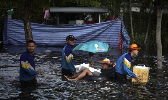 A Thai man sits inside an inflated tyre as people leave flooded areas in Bangkok, Thailand, Wednesday, Oct. 26, 2011 (AP Photo/Altaf Qadri)