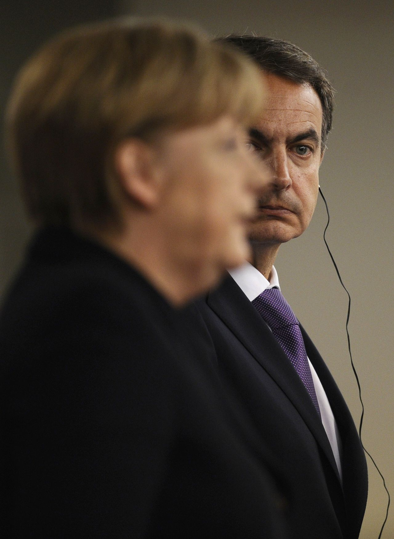 Spain's President of Government Jose Luis Rodriguez Zapatero (R) looks on as he gives a joint press conference with German Chancellor Angela Merkel during a Spain-Germany summit on February 3, 2011 at La Moncloa palace, in Madrid. AFP PHOTO/ PIERRE-PHILIPPE MARCOU
