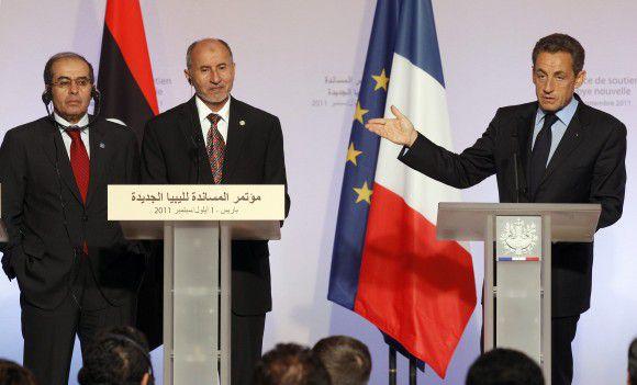 President Sarkozy (R), voorzitter van de Libische Nationale Overgangsraad Mustafa Abdel Jalil (C), en Mahmoud Jibril (L), regeringsleider van de raad, op de conferentie in Parijs. Foto Reuters / Benoit Tessier