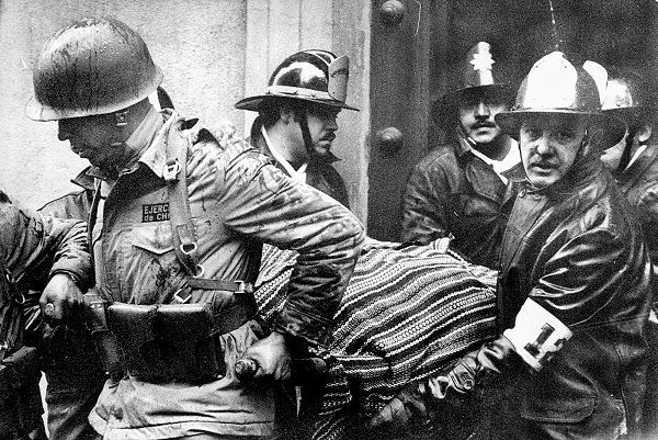 FILE - Soldiers and firefighters carry the body of President Salvador Allende, wrapped in a Bolivian poncho, out of the destroyed La Moneda presidential palace after the Sept. 11, 1973 coup led by Gen. Augusto Pinochet that ended Allende's three-year government. Chilean President Sebastian Pinera is being pressured by the daughters of two presidents whose deaths remain shrouded in mystery: Salvador Allende, who allegedly committed suicide as Pinochet's troops seized the presidential palace in 1973, and Allende's predecessor Eduardo Frei Montalva, who had become a prominent Pinochet critic and was allegedly poisoned in 1982. (AP Photo/El Mercurio, File)