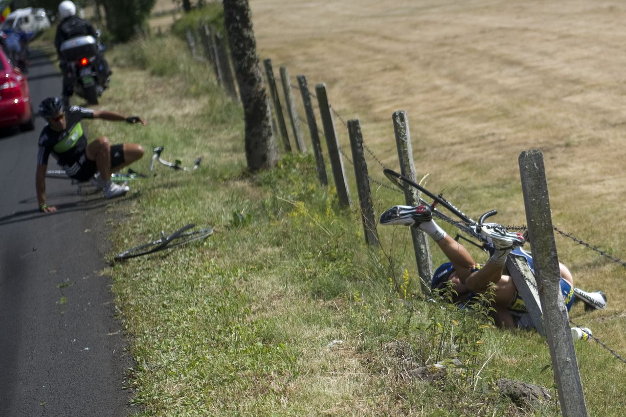One of the breakaway men, Netherland's Johnny Hoogerland (R) is seen in the barbed-wire after he crashed at the side of the road with Spain's Juan Antonio Flecha (L) during the 208 km and ninth stage of the 2011 Tour de France cycling race run between Issoire and Saint-Flour, center rance, on July 10, 2011. Hoogerland and Hoogerland survived being hit at speed by a car which bore the marking of France Televisions. AFP PHOTO / LIONEL BONAVENTURE