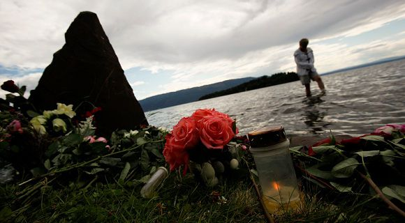 Caption: A candle is lit in commemoration of the victims of a shooting as a person walks through a lake near the Utoeya island in Sundvollen July 29, 2011, where anti-Islam extremist Anders Behring Breivik killed 68 people on Fiday last week. Breivik, 32, killed a total of 76 people in a bomb attack in central Oslo followed by the shooting rampage at the island summer camp for the ruling Labour Party's youth wing. REUTERS/Wolfgang Rattay (NORWAY - Tags: CIVIL UNREST CRIME LAW)