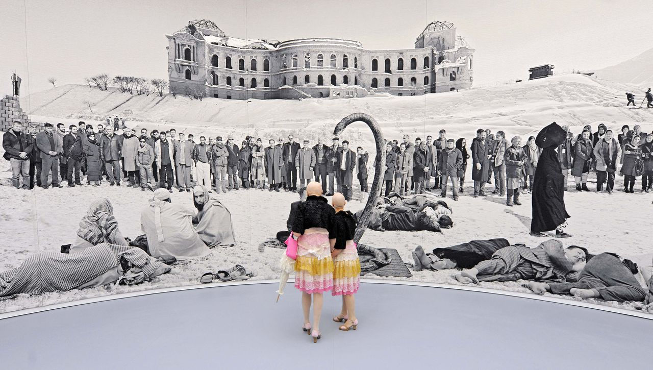 Performers 'Eva and Adele' walk in front of an art tapestry to the Afghanistan theme 'Of what is, that it is; of what is not, that is it not' (2012) of British based artist Goshka Macuga during the press preview of the dOCUMENTA (13) in Kassel, Germany, Wednesday, June 6, 2012. For 100 days, over 150 artists from 55 countries and other participants from around the world will gather and present their works. The 13th edition of the 'dOCUMENTA' international contemporary arts exhibition, which is held once every five years, will be open to public from June 9 until Sept. 16, 2012. (AP Photo/Jens Meyer)