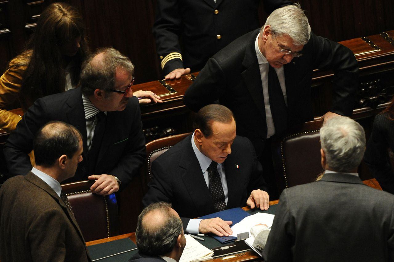 Italy's Prime Minister Silvio Berlusconi (C) and his ministers look at the figures following a vote on Italy's public accounts at the parliament on November 8, 2011 in Rome. Prime Minister Silvio Berlusconi's main coalition partner, Umberto Bossi, called for his resignation the same day ahead of a knife-edge vote as Italy came under acute pressure from record borrowing rates to finance debt. AFP PHOTO / VINCENZO PINTO