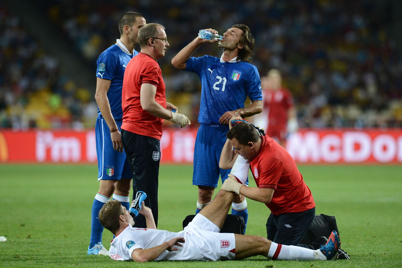 English midfielder Steven Gerrard is treated by trainers as Italian midfielder Andrea Pirlo drinks during the Euro 2012 football championships quarter-final match England vs Italy on June 24, 2012 at the Olympic Stadium in Kiev. AFP PHOTO / CARL DE SOUZA