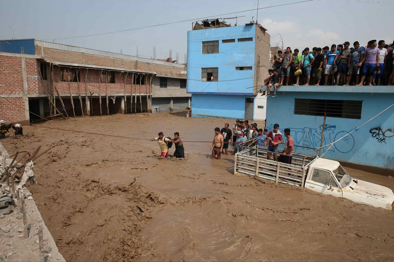 Politieagenten redden mensen van het water tijdens hevige overstromingen in Lima, de hoofdstad van Peru.