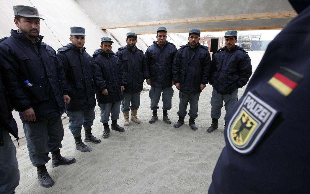 Afghan national policemen listen to instructions of a German federal policeman at the shooting range of the police training centre near the German Bundeswehr army camp in Kunduz, December 7, 2010. The team of German federal policemen is conducting an ongoing training program for the Afghan national police (ANP). REUTERS/Fabrizio Bensch (AFGHANISTAN - Tags: MILITARY CONFLICT)