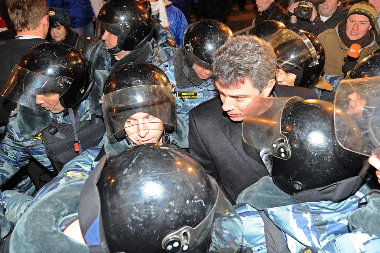 Riot police encircle Russian opposition leader Boris Nemtsov (C), detained while taking part in an unauthorized rally, on Triumfalnaya Square in central Moscow, late on December 6, 2011. Opposition leaders defied the Russian authorities today by organizing a second mass protest in two days against Vladimir Putin's 12-year rule, despite warnings of a police crackdown and the jailing of one of the organizers. AFP PHOTO / KIRILL KUDRYAVTSEV