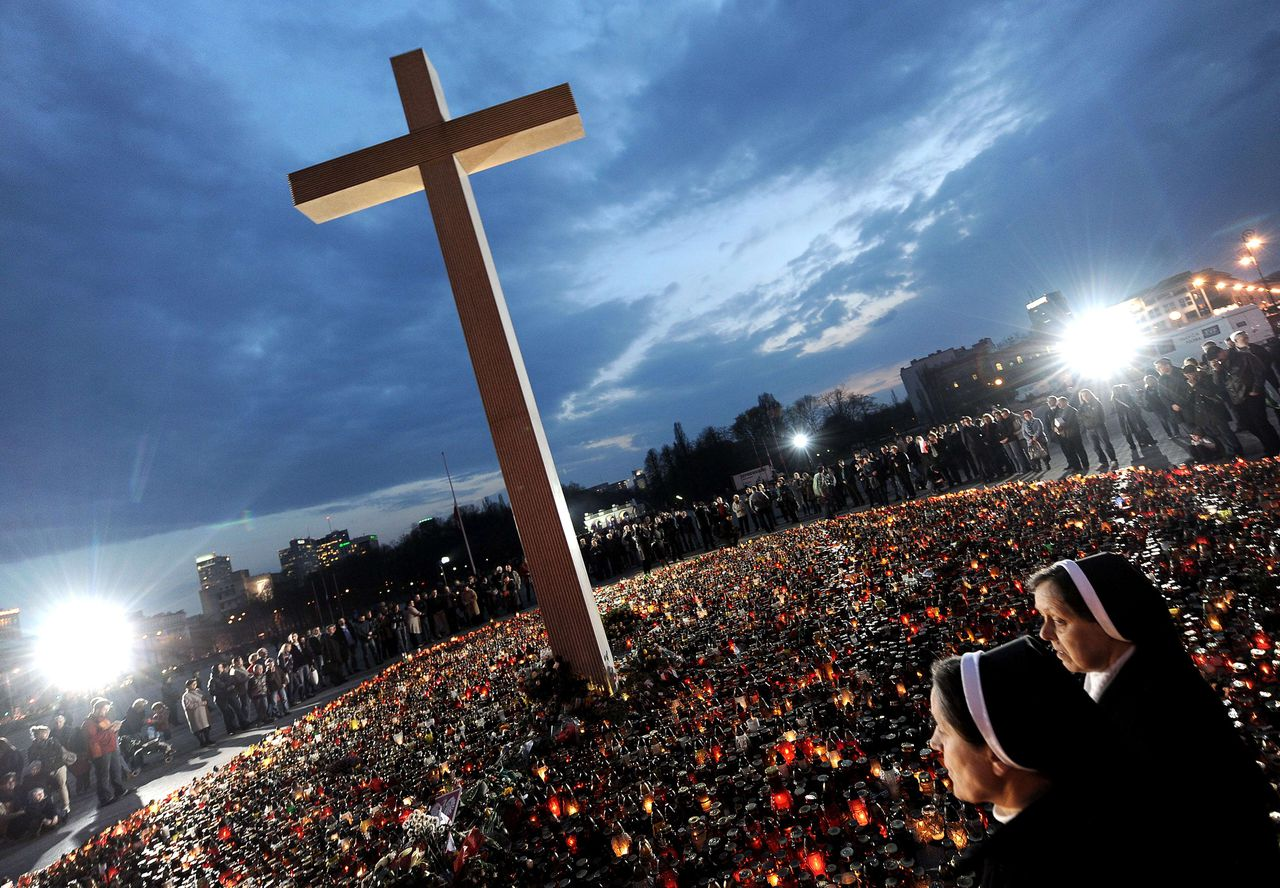 Poolse herdenking van het vliegtuigongeluk in april waarbij de president omkwam; op het web voer voor vele complottheorieën. Foto AFP AFP PICTURE OF THE YEAR 2010 Polish nuns pray under a giant cross at Pilsudski Square on April 12, 2010 in a tribute to victims of the air-crash in which President Lech Kaczynski was killed on April 10. Russia united with Poland in mourning President Lech Kaczynski and 95 other victims of a weekend plane crash, as authorities helped grieving Polish relatives identify loved ones. AFP PHOTO/JOE KLAMAR