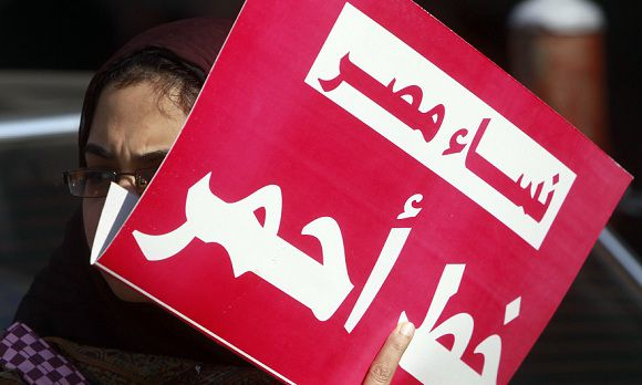 "Caption: A woman holds a sign that reads ""Egypt women red line"" as they protest against military council violations and virginity tests against females outside the State Council court and in support of Samira Ibrahim in Cairo, December 27, 2011. An Egyptian court ordered on Tuesday that forced virginity tests be stopped on female detainees in military prisons. The case was filed by Samira Ibrahim, a woman who said the army forced her to undergo a virginity test in March after she was arrested during a protest in Cairo's Tahrir Square. REUTERS/Amr Abdallah Dalsh (EGYPT - Tags: CIVIL UNREST POLITICS)"
