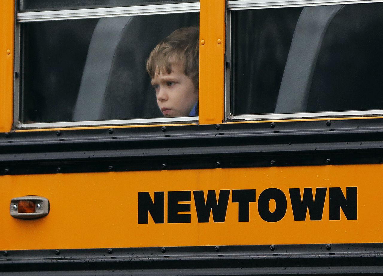 A child looks out of the window of a school bus carrying students from the Newtown school district as it makes its way past the funeral for Sandy Hook student James Mattioli, at the Saint Rose of Lima church in Newtown, Connecticut December 18, 2012. Twelve girls, eight boys and six adult women were killed in a shooting on Friday at Sandy Hook Elementary School in Newtown. REUTERS/Shannon Stapleton (UNITED STATES - Tags: CRIME LAW EDUCATION)