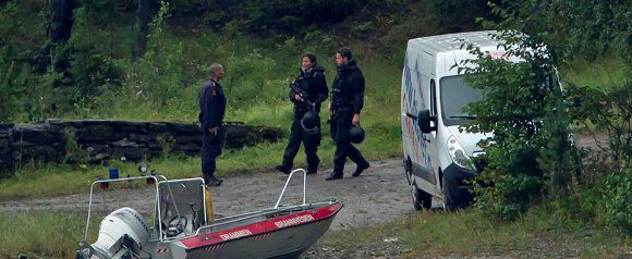 Caption: Armed police officers are seen on the island of Utoya, Norway Saturday, July 23, 2011. The 32-year-old man suspected in bomb and shooting attacks that killed at least 91 people in Norway bought six tons of fertilizer before the massacres, the supplier said Saturday as police investigated witness accounts of a second shooter. Norway's prime minister and royal family visited grieving relatives of the scores of youth gunned down in a horrific killing spree on an idyllic island retreat. A man who said he was carrying a knife was detained by police officers outside the hotel, as the shell-shocked Nordic nation was gripped by reports that Norwegian gunman may not have acted alone. (AP Photo/Matt Dunham)