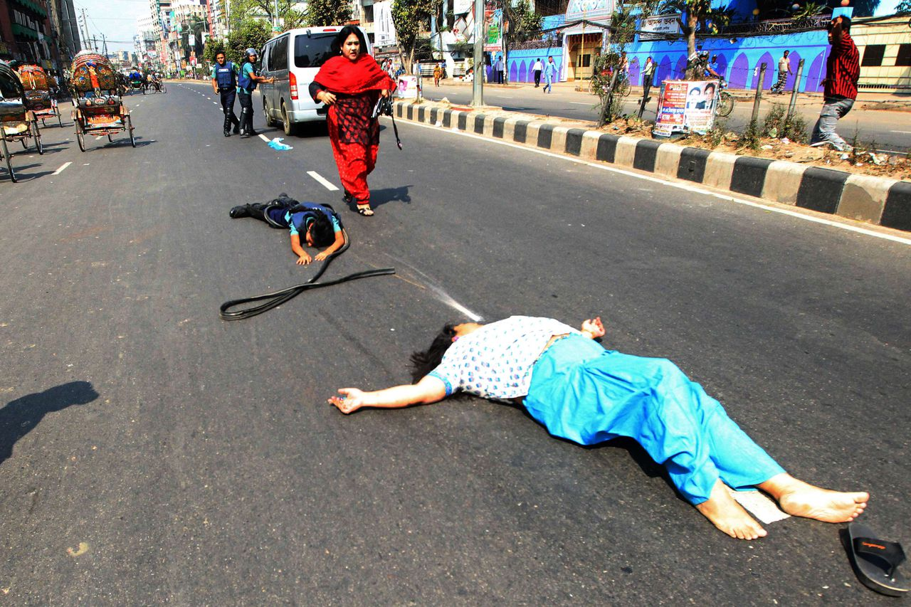 Bangladesh Nationalist Party lawmaker Shammi Akter (L) and a police official lie on the road after they lost balance and fell from a police van, which was transporting Akter following her arrest, during a nationwide strike, called by the main opposition Bangladesh Nationalist Party, in Dhaka on March 6, 2013. Four female BNP lawmakers were detained in front of their party's headquarters at Naya Paltan as the party-enforced daylong strike began on March 7. AFP PHOTO/STR