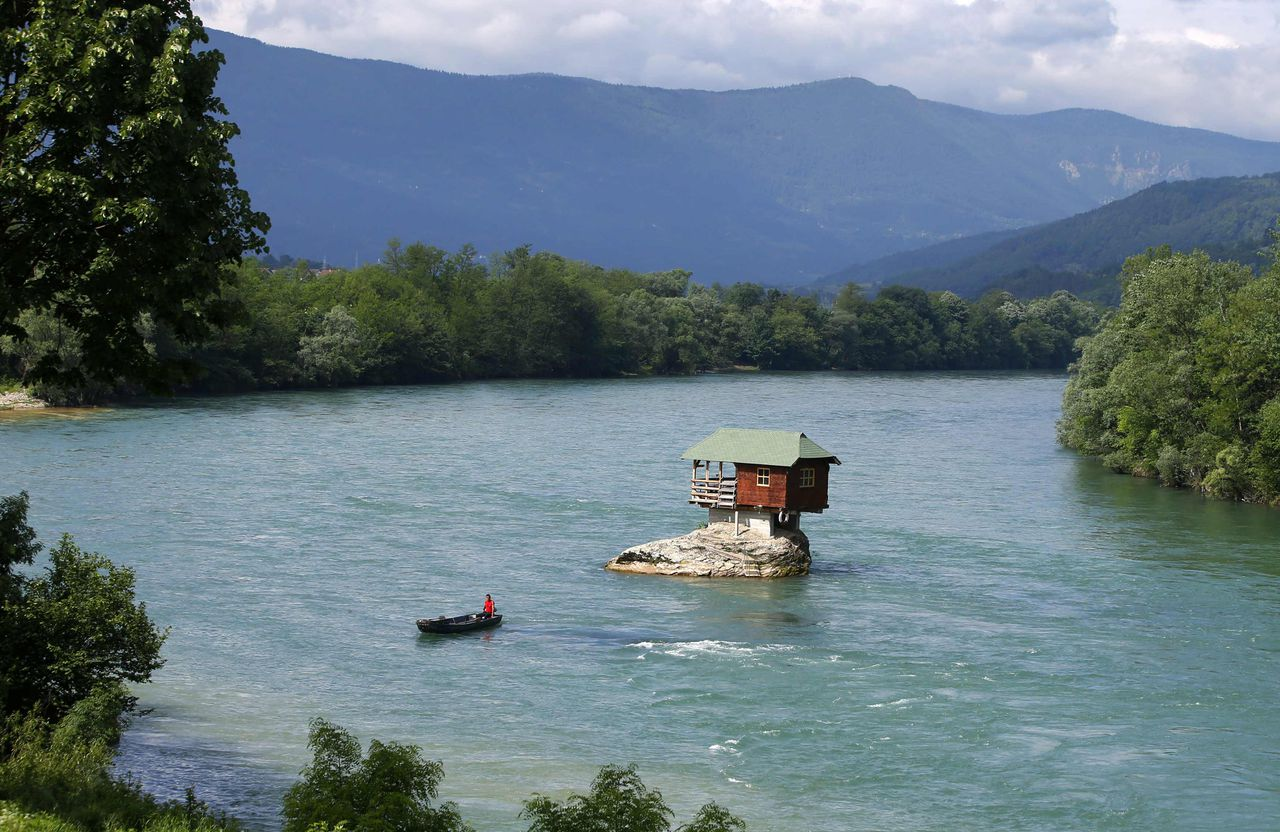 A man rows a boat near a house built on a rock on the river Drina near the western Serbian town of Bajina Basta, about 160km (99 miles) from the capital Belgrade May 22, 2013. The house was built in 1968 by a group of young men who decided that the rock on the river was an ideal place for a tiny shelter, according to the house's co-owner, who was among those involved in its construction. REUTERS/Marko Djurica (SERBIA - Tags: ENVIRONMENT SOCIETY TRAVEL)