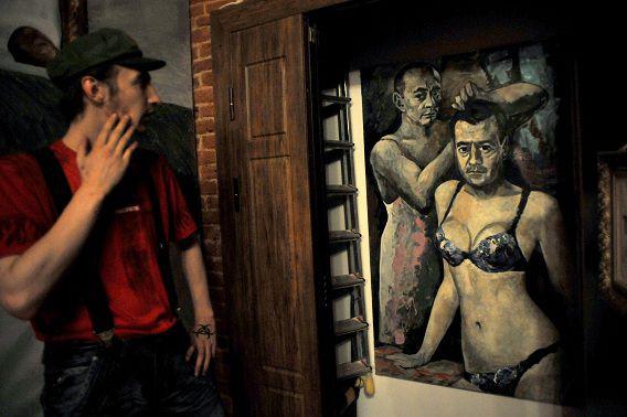 Een bezoeker kijkt naar het controversiële schilderij.