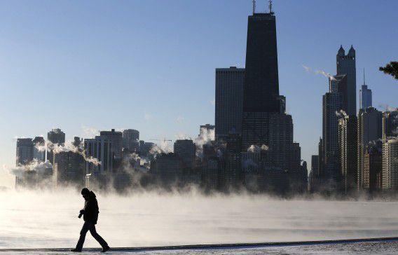 Een man loopt langs de oever van Lake Michigan in Chicago, Illinois. Het is in het noordoosten van de VS ongewoon koud.