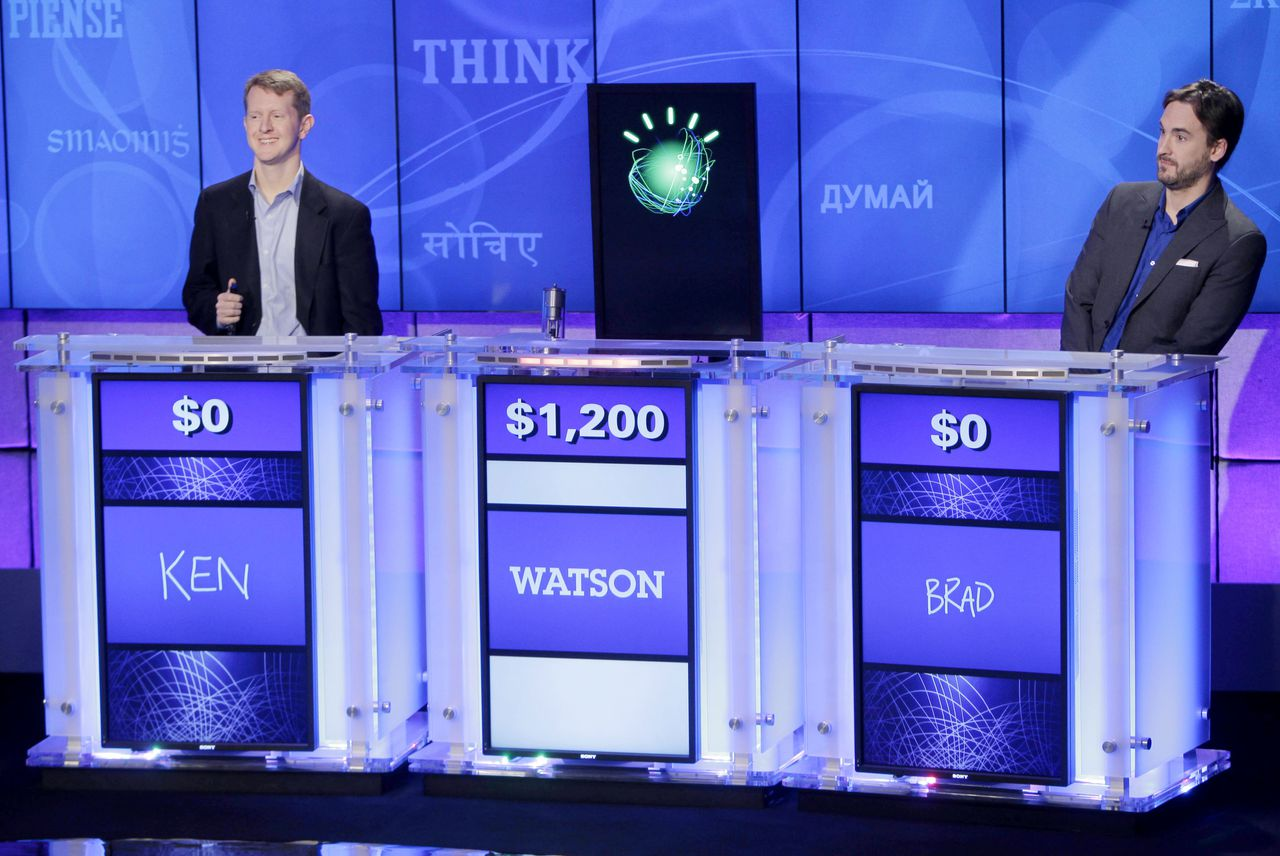 """Jeopardy!"" champions Ken Jennings, left, and Brad Rutter, right, look on as an IBM computer called ""Watson"" beats them to the buzzer to answer a question during a practice round of the ""Jeopardy!"" quiz show in Yorktown Heights, N.Y., Thursday, Jan. 13, 2011. It's the size of 10 refrigerators, and it swallows encyclopedias whole, but an IBM computer was lacking one thing it needed to battle the greatest champions from the ""Jeopardy!"" quiz TV show - it couldn't hit a buzzer. But that's been fixed, and on Thursday the hardware and software system named Watson played a competitive practice round against two champions. A ""Jeopardy!"" show featuring the computer will air in mid-February, 2011. (AP Photo/Seth Wenig)"