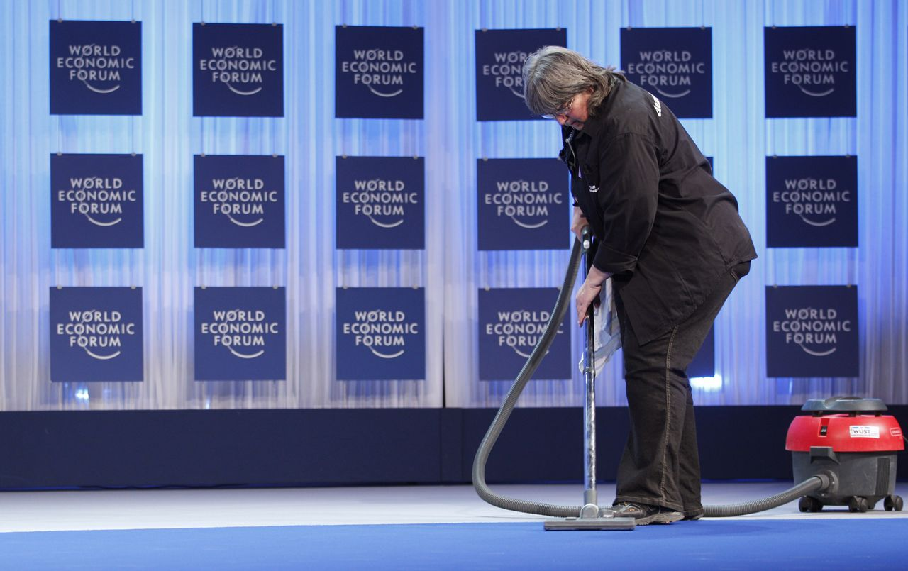 Schoonmaker in congreszaal van World Economic Forum. Foto Reuters A worker vacuums the stage of the plenary hall at the Congress Center in Davos January 25, 2011. The annual meeting of the WEF takes place under heavy security measures from January 26 to 30 in the Alpine resort, and will be attended by top politicians, monetary policymakers and senior business executives. REUTERS/Christian Hartmann (SWITZERLAND - Tags: POLITICS BUSINESS)