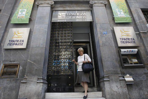 A woman walks out of a Piraeus bank branch in central Athens in this May 30, 2012 file photo. To match Special Report GREECE-BANKS/ REUTERS/John Kolesidis/Files (GREECE - Tags: BUSINESS POLITICS)