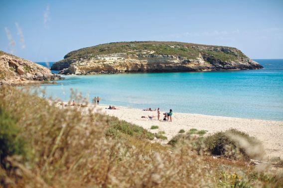 De kust van Lampedusa, een voormalig toeristenparadijs. Inwoners komen tegenwoordig vooral asielzoekers te hulp