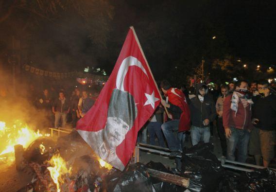 Turkse demonstranten met de nationale vlag in de hand met een afbeelding van Kemal Ataturk, de grondlegger van de republiek Turkije, voordat zij op de vuist gingen met de oproerpolitie.