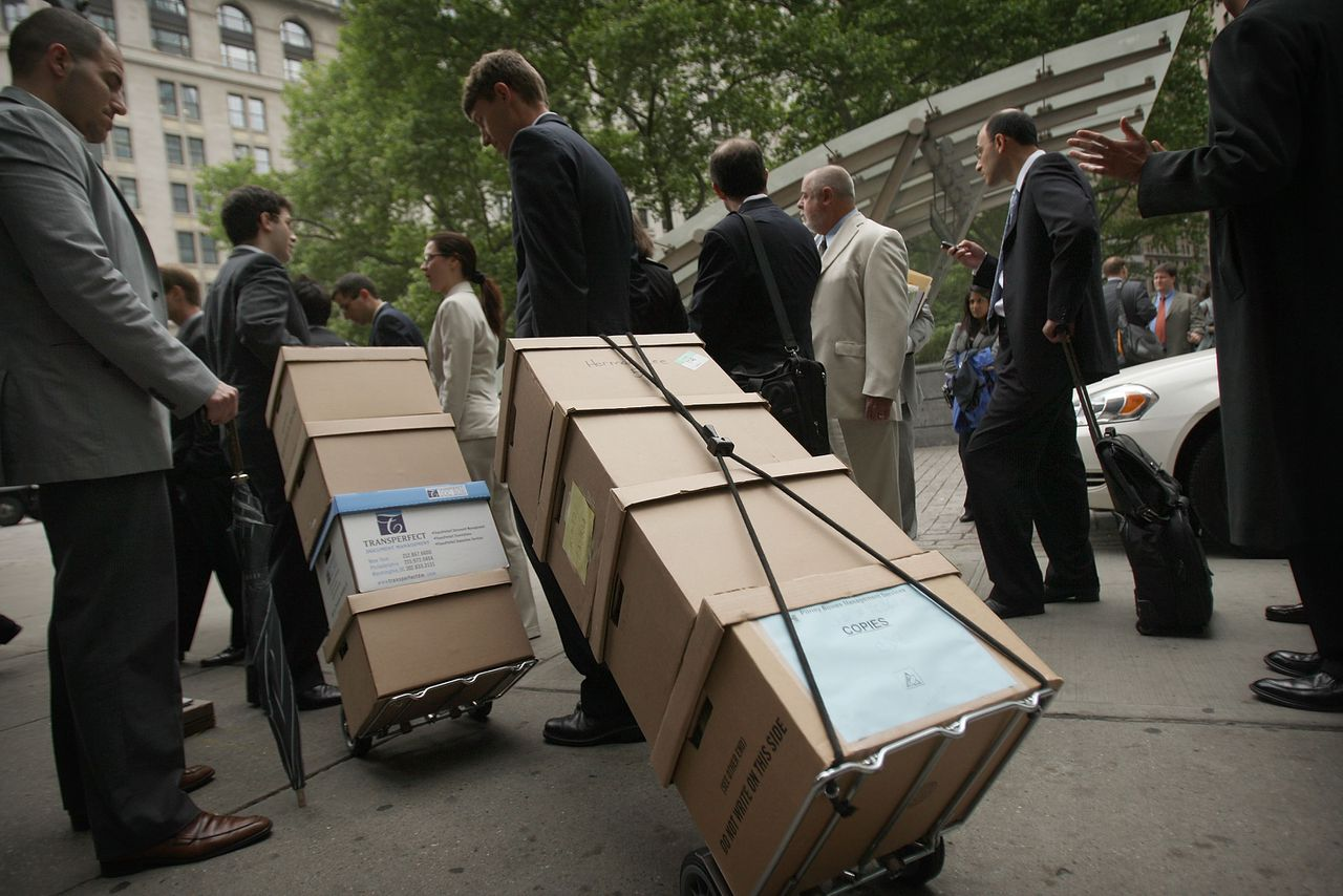 advocaten die met steekwagens documenten over General Motors de New Yorkse faillissementsrechtbank binnendragen. NEW YORK - MAY 27: Lawyers with boxes of documents invoved with General Motors bankruptcy proceedings line-up outside the United States Bankruptcy Court for the Southern District of New York on May 27, 2009 in New York City. General Motors moved closer to bankruptcy following a rejection by bond holders of a debt exchange offer. In morning trading news of the failed bond exchange offer sent its shares down 12 cents, or 8.3 percent, to $1.32. Spencer Platt/Getty Images/AFP == FOR NEWSPAPERS, INTERNET, TELCOS & TELEVISION USE ONLY ==
