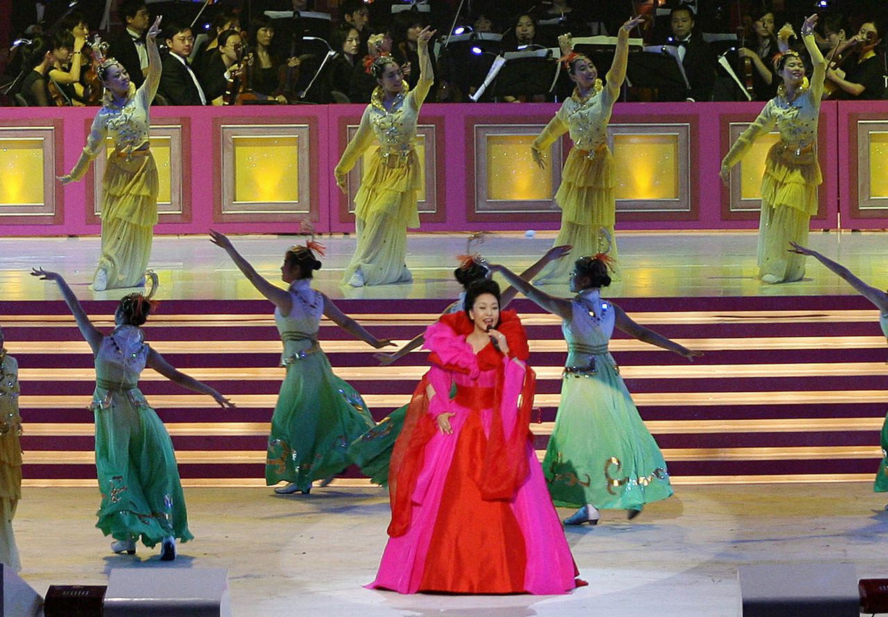 (FILES) In a file picture taken on June 30, 2007, Chinese singer Peng Liyuan performs during the Grand Variety Show in Hong Kong, in celebration of the 10th anniversary of the Reunification. China's next first lady Peng Liyuan is a dazzling singer whose profile long eclipsed that of her husband Xi Jinping, and who will bring a touch of glamour to a role hidden in the shadows for decades. AFP PHOTO / TED ALJIBE / FILES