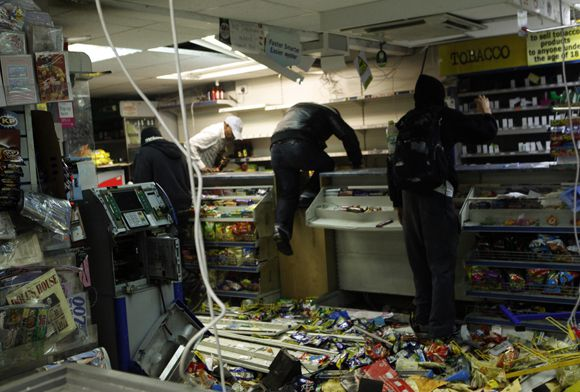 Looters rampage through a convenience store in Hackney, east London August 8, 2011. Youths hurled missiles at police in northeast London on Monday as violence broke out in the British capital for a third night. REUTERS/Olivia Harris (BRITAIN - Tags: CRIME LAW CIVIL UNREST IMAGES OF THE DAY)