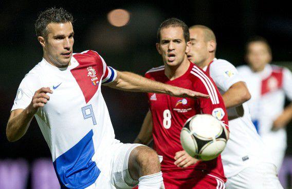 Robin van Persie (links) in duel met Marcio Vieira van Andorra tijdens het WK-kwalificatieduel in Estadi Comunal.