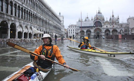 A couple canoes in the flooded Saint Mark's Square in Venice November 6, 2011. REUTERS/Manuel Silvestri (ITALY - Tags: ENVIRONMENT TPX IMAGES OF THE DAY SOCIETY)