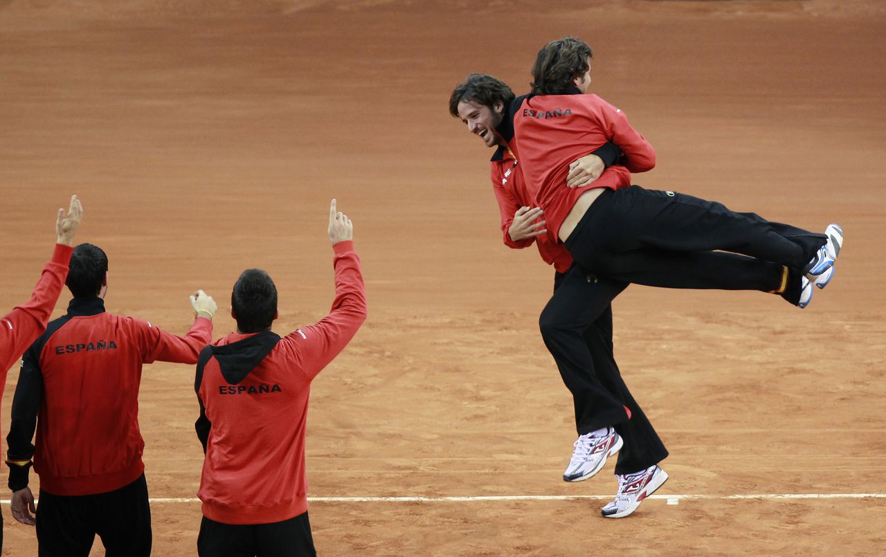 Spain's team celebrates after defeating Argentina at their Davis Cup final reverse singles rubber at the Olympic Stadium in Seville December 4, 2011. Rafael Nadal mounted a thrilling comeback back from a set down to beat Argentina's Juan Martin Del Potro and clinched Spain's fifth Davis Cup tennis title on Sunday. REUTERS/Javier Diaz (SPAIN - Tags: SPORT TENNIS)