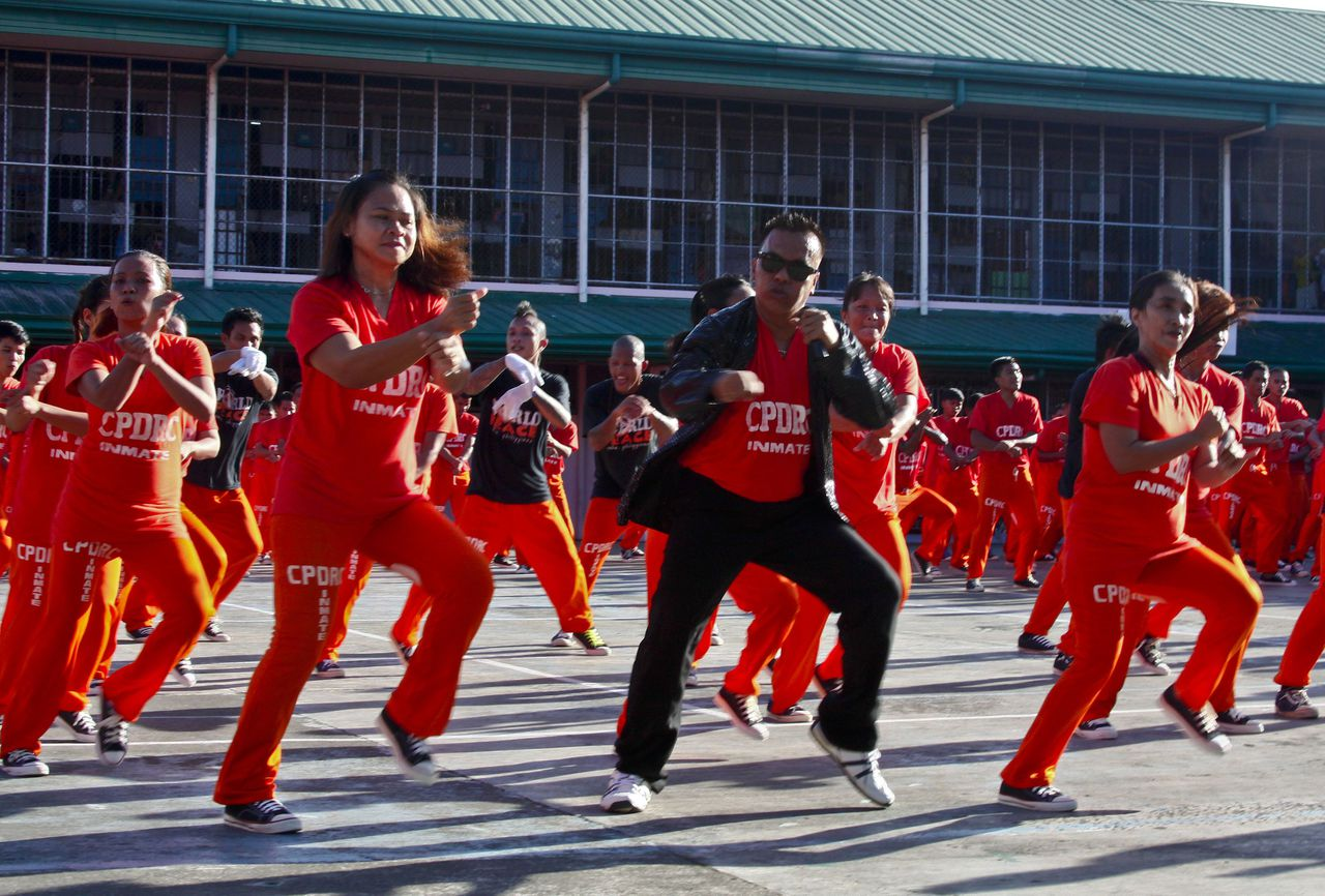 "Philippine convicts dance to the tune of the horse-riding dance ""Gangnam Style"" made famous by South Korean rapper Psy during a performance for visitors and toruists at the Provincial Detention and Rehabilitation Center in Cebu on October 27, 2012. Philippine convicts who became famous for dancing to Michael Jackson's hits have added South Korean spice to their repertoire, with a performance of the popular ""Gangnam Style"" rap. AFP PHOTO"