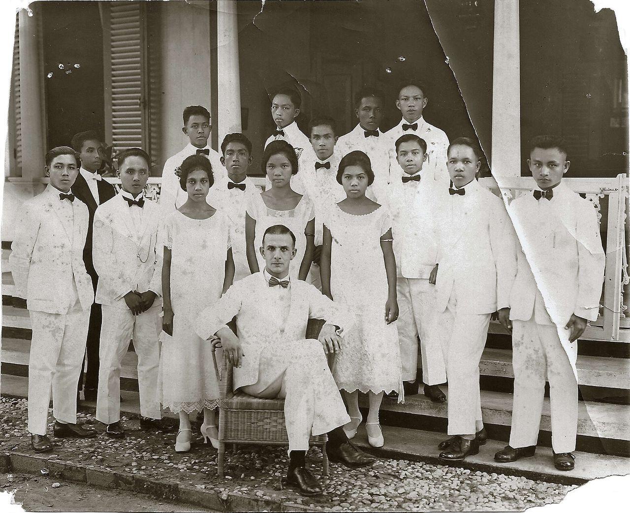 Dominee Ernst de Vreede bij de pastorie in Ambon Stad op 12 april 1926. Echtgenote Henny de Vreede-Bomers, die kort daarna vermoord werd, schreef over dit portret in een brief aan haar familie in 1926: 'Een van de aannemelingen moest al van het avondmaal geweerd worden wegens onzedelijkheid, maar de aanklacht was met zoveel laster en haat omgeven, dat ook de beschuldigers dezelfde straf trof. Ja, 't blijven inlanders. Vanmiddag komen ze allemaal met Ernst op het portret.'