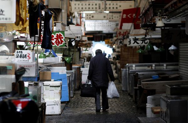 A man walks after shopping at the Tsukiji fish market in Tokyo March 19, 2011. Fishmongers at the popular market reported that the number of customers and amount of sales were sharply down due to fears about blackouts and the nuclear disaster in northern Japan following last weeks earthquake and tsunami. REUTERS/Toru Hanai (JAPAN - Tags: DISASTER FOOD BUSINESS)