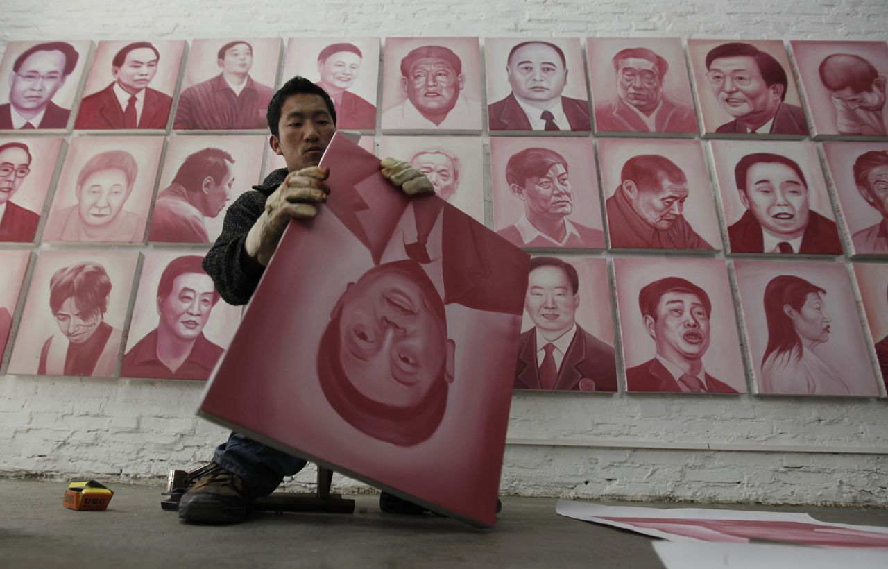 """An assistant puts a portrait of toppled former Shenzhen Mayor Xu Zongheng on a frame for Chinese artist and film-maker Zhang Bingjian's """"Hall of Fame"""" project in his studio in Beijing April 28, 2011. The stark, monochromatic portraits rendered in the reddish-pink hue of China's 100 yuan banknotes, painted by a team of artists in Shenzhen's Dafen village -- known for its mass-produced knock-offs of iconic Western paintings -- are the brainchild of outspoken Zhang. To match Reuters Life! CHINA-ART/CORRUPTION REUTERS/Jason Lee (CHINA - Tags: BUSINESS SOCIETY POLITICS)"""