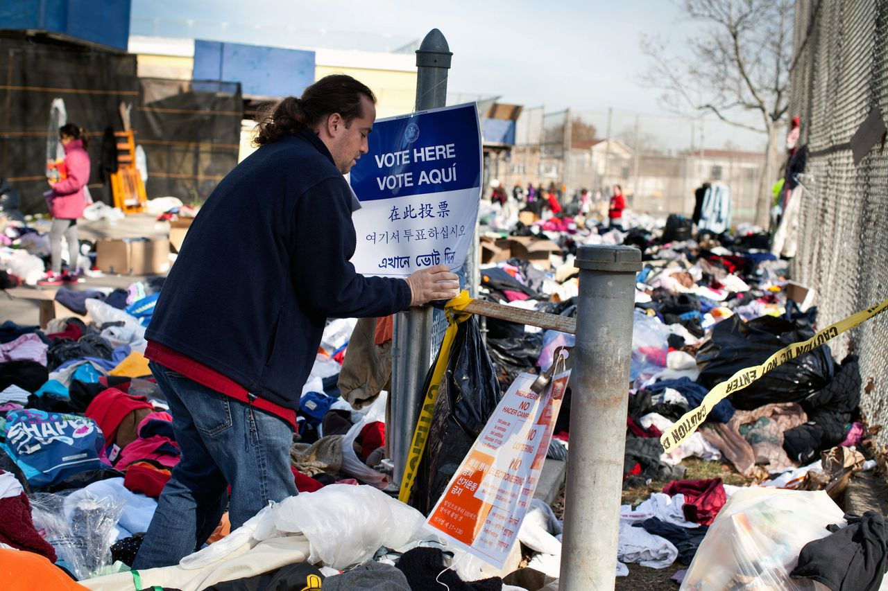 A poll worker puts up a sign among mounds of clothing left as donations outside a makeshift polling location at PS52 in the Midland Beach neighborhood of the Staten Island borough of New York, U.S., on Tuesday, Nov. 6, 2012. U.S. President Obama is seeking to overcome the drag of high unemployment and economic weakness that has frustrated predecessors' re-election bids, while his Republican rival Mitt Romney reaches for an upset to propel him beyond his party's standing and swamp an electoral map stacked against him on the final day of the presidential race. Photographer: Emile Wamsteker/Bloomberg