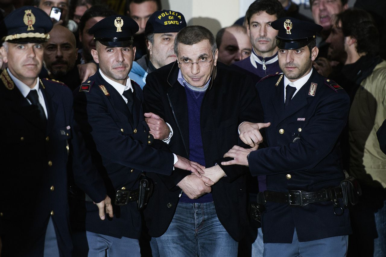 Italian policemen escort Michele Zagaria (C), the boss of the Casalesi clan outside the Police's headquarters in Caserta following his arrest on December 7, 2011. Italian police on Wednesday arrested Michele Zagaria, 53, the most senior boss of the Camorra mafia still at large, digging through a secret bunker near Naples to end his 16 years on the run. AFP PHOTO / ROBERTO SALOMONE