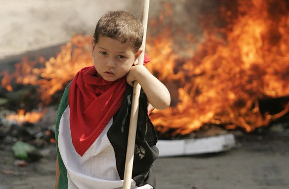 """TOPSHOTS-A Palestinian child stands next burning tires at the Palestinian refugees camp of Ain al-Helweh on the outskirts of the southern Lebanese city of Sidon on June 6, 2011 during a """"Day Of Rage"""" that called on all the Palestinian factions in Lebanon to show their support to the Palestinians and others killed by Israeli soldiers during the rallies witnessed along the ceasefire line with Israel in the Golan Heights yesterday and inside the West Bank. AFP PHOTO/MAHMOUD ZAYYAT"""