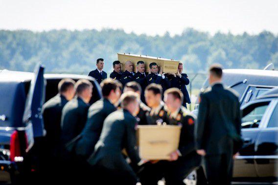Militairen dragen op vliegbasis Eindhoven kisten met daarin de lichamen van slachtoffers van de vliegramp.