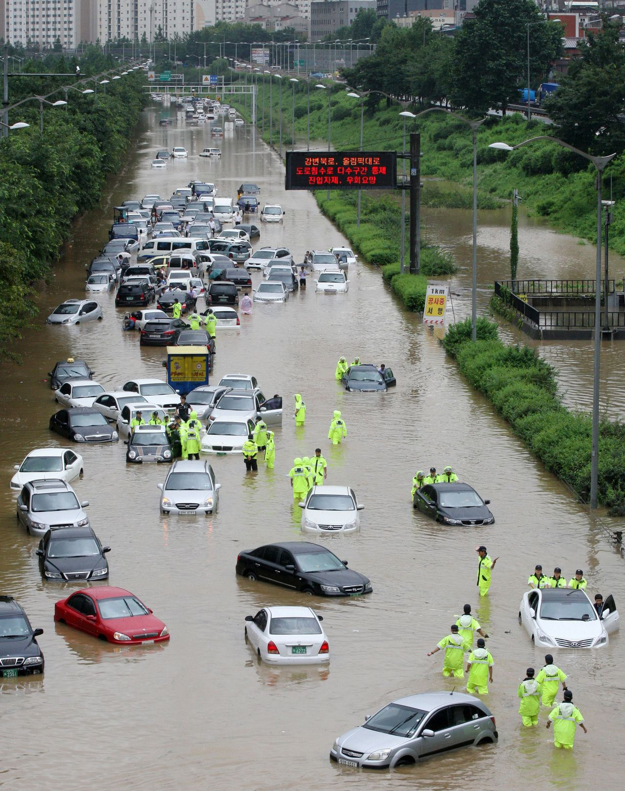 Cars are submerged by floodwaters along a street after heavy rains hit the Seoul region on July 27, 2011. Torrential rain pounding South Korea triggered landslides which killed 22 people, flooded hundreds of homes and turned main roads into rivers of churning, muddy water. AFP PHOTO / YANG HOE-SEONG