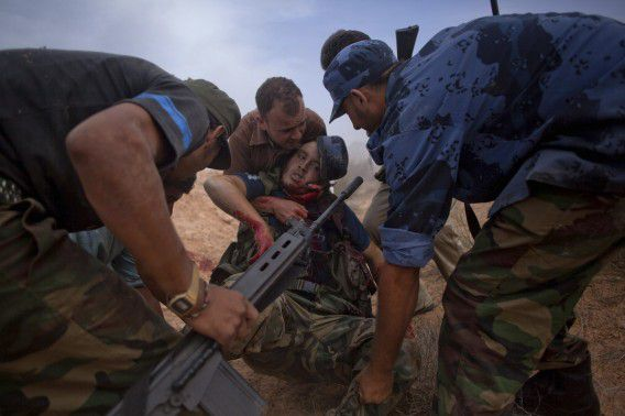 Libyan revolutionary fighters carry a wounded comrade while attacking pro-Gadhafi forces in Sirte, Libya, Friday, Oct. 7, 2011. Rebel forces have besieged Sirte since September 15 but have not managed to penetrate the heart of the city because of fierce resistance from loyalists inside the home town of Libya's ousted leader Moammar Gadhafi. (AP Photo/Manu Brabo)