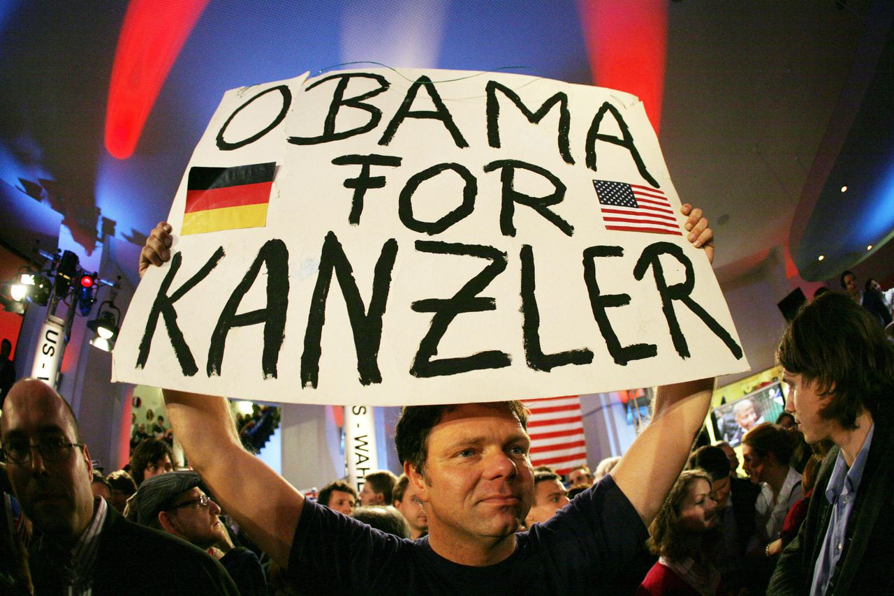"""Verkiezingsavond op een rechtenfaculteit in Hamburg. ?Verwacht niet dat Obama een Europese president wordt.? (Foto AFP) A guest holds up a banner reading """"Obama for Chancellor"""" during an election night at the Bucerius Law School in Hamburg, northern Germany, on November 4, 2008. Americans crowd polling stations on November 4 to vote in their historic election, with front-running Democrat Barack Obama fighting to be the first black US president and Republican John McCain hoping for an upset win. AFP PHOTO DDP/ ROLAND MAGUNIA GERMANY OUT"""
